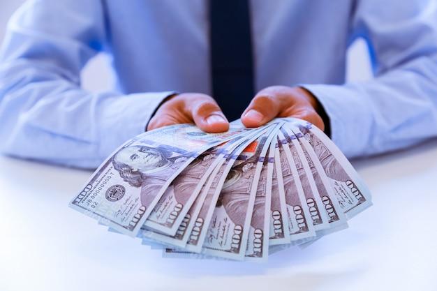 Homem de negócios com dinheiro à disposição, dólar americano, investimento, sucesso e conceitos de negócio rentável.
