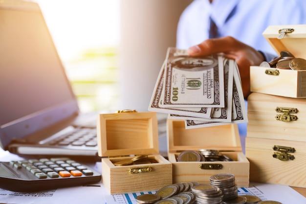 Homem de negócios com dólares do dinheiro - conceito do negócio, computador e finança, investimento, economias.