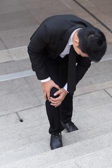 Homem de negócios com dor no joelho, conceito de obstáculo
