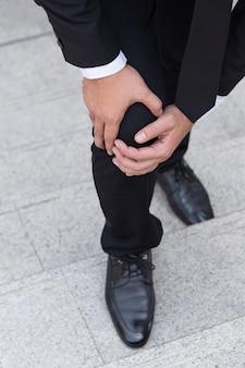 Homem de negócios com dor no joelho, conceito de obstáculo Foto Premium