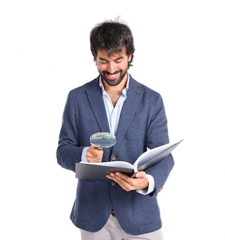 Homem de negócios com lupa redingando um livro sobre fundo branco