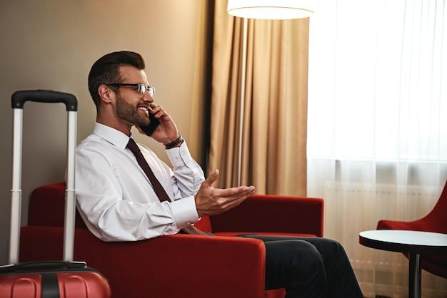 Homem de negócios com mala e smartphone sentado no sofá do quarto do hotel