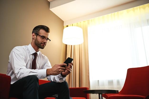 Homem de negócios com mala e smartphone sentado no sofá na sala do hotel