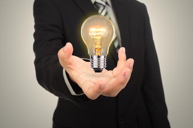 Homem de negócios com mão rígidos e uma lâmpada acesa
