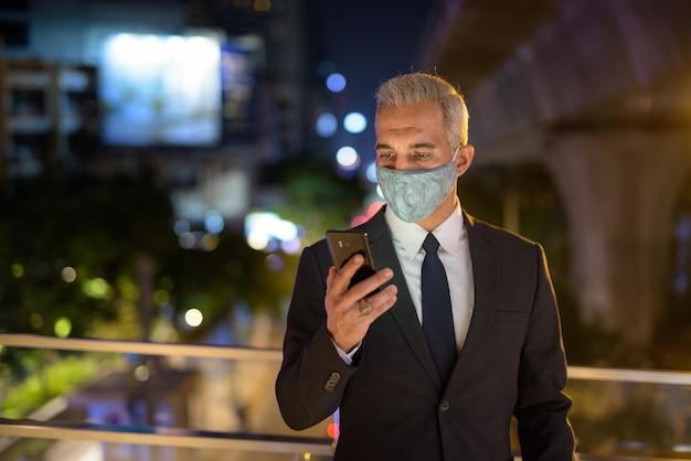 Homem de negócios com máscara facial protetora na cidade à noite usando telefone