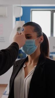 Homem de negócios com máscara protetora, verificando a temperatura dos colegas usando termômetro infravermelho para evitar a infecção do vírus. colegas de trabalho mantendo distância social para prevenir a propagação do coronavírus