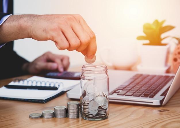 Homem de negócios com moeda escrever custo e finanças. salvando o conceito de dinheiro.