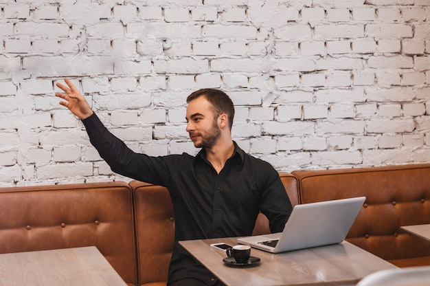 Homem de negócios com o laptop levantou a mão no café, chamando o garçom