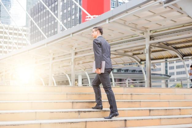 Homem de negócios com o laptop subindo as escadas em uma hora do rush para trabalhar. tempo de pressa.