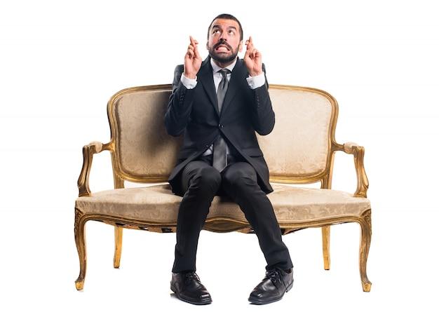 Homem de negócios com os dedos cruzados