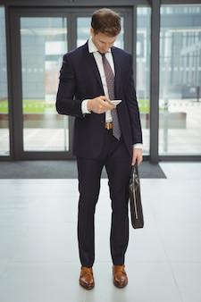 Homem de negócios com pasta usando telefone celular