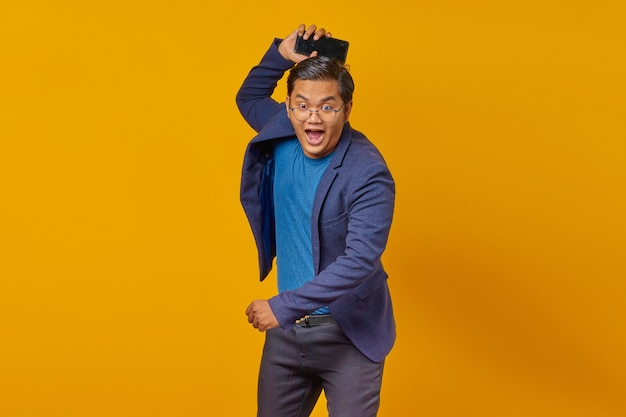 Homem de negócios com raiva com smartphone jogando gesto sobre fundo amarelo