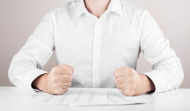 Homem de negócios com raiva, punhos, relatório financeiro