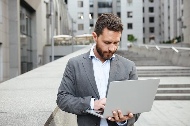 Homem de negócios com roupa formal segurando um laptop prateado aberto em frente a um prédio comercial na área urbana