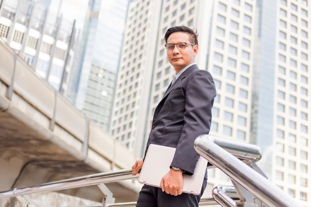 Homem de negócios com seu laptop subindo as escadas em uma hora do rush para trabalhar. tempo de pressa.