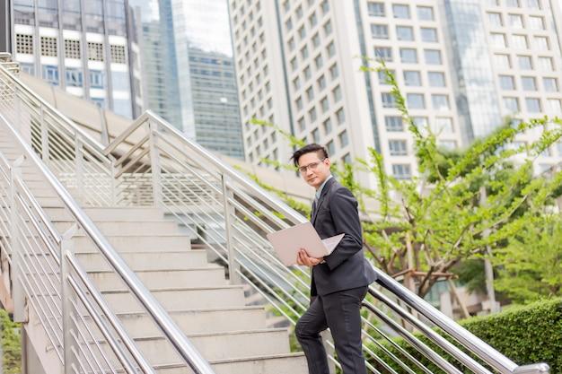 Homem de negócios com seu laptop subindo as escadas em uma hora do rush para trabalhar