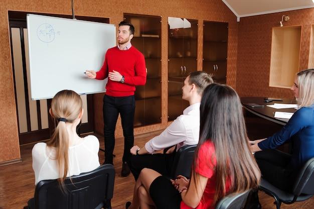 Homem de negócios com sua equipe, grupo de pessoas em segundo plano no escritório moderno brilhante dentro de casa.