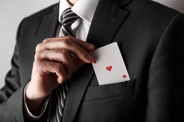 Homem de negócios com um ás no bolso da jaqueta.
