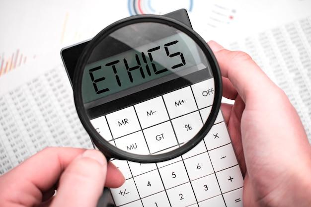 Homem de negócios com uma calculadora na mão com a palavra ética