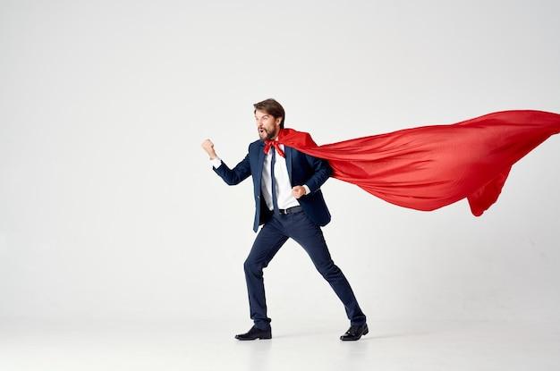 Homem de negócios com uma capa vermelha em um espaço claro olha para o lado terno de super-herói de sucesso