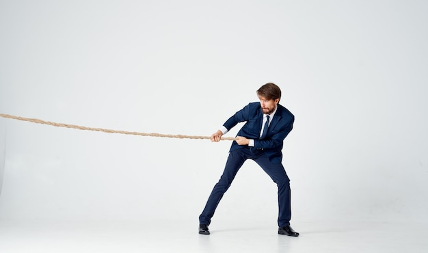 Homem de negócios com uma corda nas mãos, modelo de tensão para atingir a meta