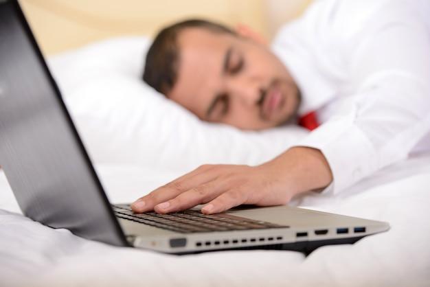 Homem de negócios com uma mala de viagem que dorme na cama na sala de hotel.