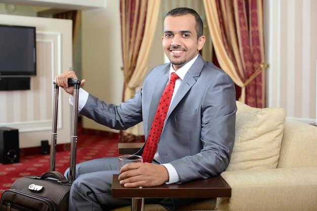 Homem de negócios com uma mala de viagem, sentando-se na cadeira no quarto de hotel.
