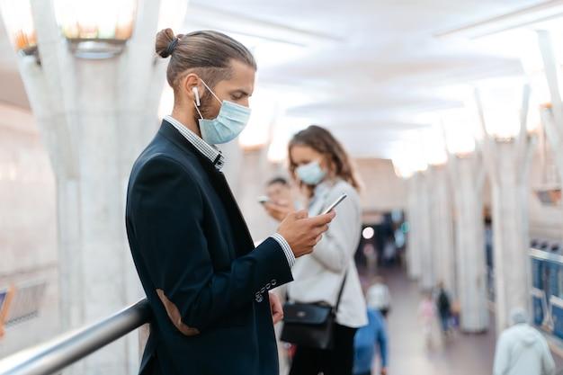 Homem de negócios com uma máscara protetora à espera de um trem no metrô.