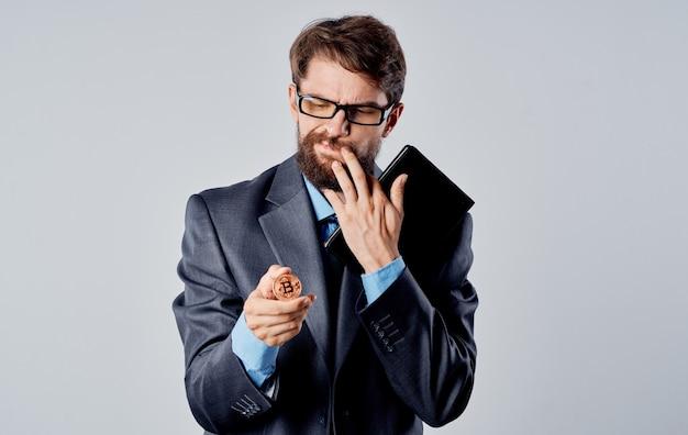 Homem de negócios com uma moeda nas mãos e um olhar perplexo gesticula com as mãos a criptomoeda bitcoin. foto de alta qualidade