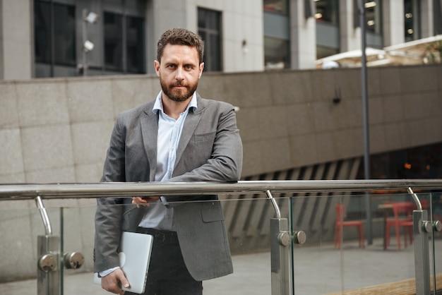 Homem de negócios confiante com roupa formal, segurando um laptop prateado fechado na mão, em frente a um prédio comercial na área urbana