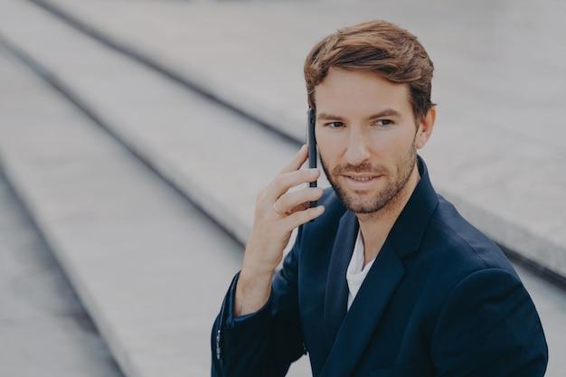Homem de negócios confiante e atraente de terno falando no smartphone do lado de fora