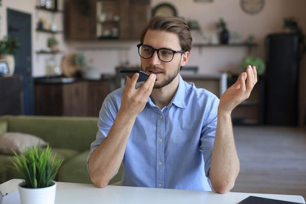 Homem de negócios confiante em copos segurando o smartphone perto da boca para gravar mensagem de voz ou ativar o assistente digital.