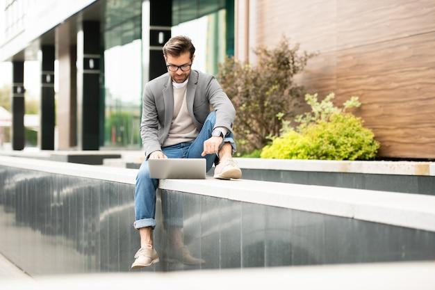 Homem de negócios confiante em roupas casuais elegantes sentado em frente ao laptop enquanto faz networking ou bate-papo por vídeo em ambiente urbano