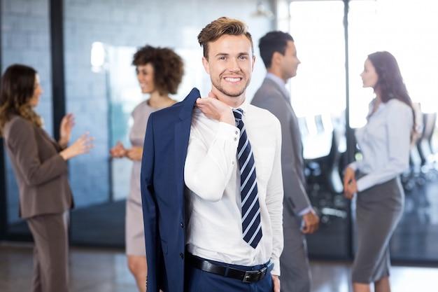 Homem de negócios confiante olhando enquanto seus colegas interagindo uns com os outros