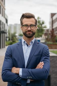 Homem de negócios confiante usando óculos elegantes de terno em pé na rua negócio de sucesso