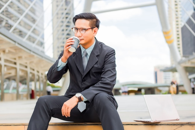 Homem de negócios considerável asiático novo que bebe o café quente na cidade moderna.