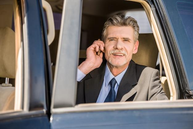 Homem de negócios considerável maduro que sai de seu carro luxuoso.