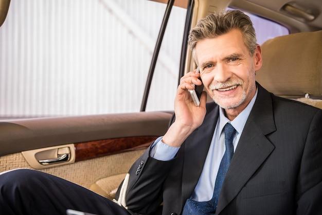 Homem de negócios considerável maduro que senta-se em seu carro luxuoso.