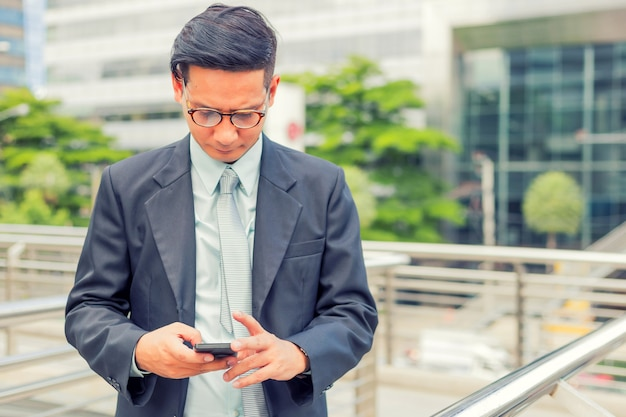 Homem de negócios considerável novo de ásia com seu smartphone que está na passagem da cidade moderna