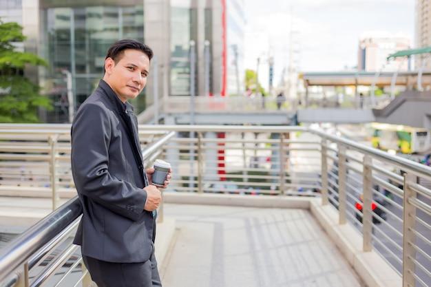 Homem de negócios considerável novo de ásia que bebe o café quente na cidade moderna