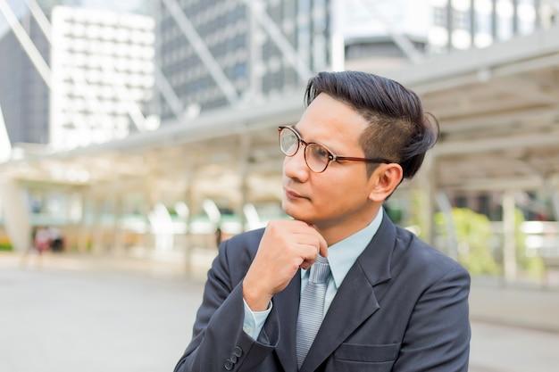 Homem de negócios considerável novo de ásia que pensa sobre seu negócio