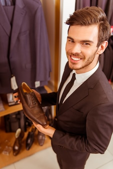 Homem de negócios considerável que sorri e que guarda sapatas clássicas.