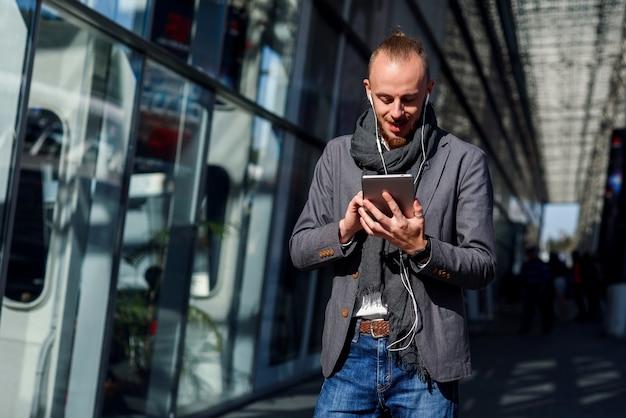 Homem de negócios considerável que trabalha em um tablet pc durante o almoço perto do centro moderno do escritório ao ar livre. conceito de tecnologias modernas, reunião de negócios, negócios, wall street.