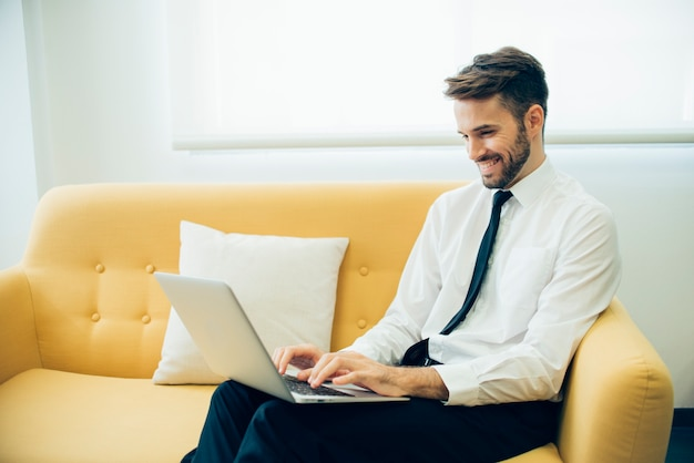 Homem de negócios considerável rindo e trabalhando com seu laptop