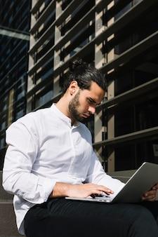 Homem de negócios considerável sério que senta-se fora do escritório que datilografa no portátil