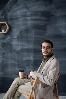 Homem de negócios contemporâneo com um copo de café sentado na cadeira isolado no espaço do quadro-negro