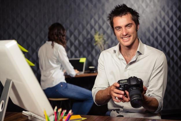 Homem de negócios criativo, olhando a foto na câmera