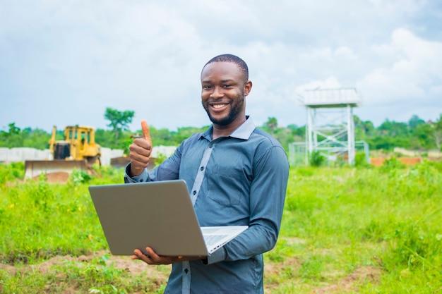 Homem de negócios da áfrica negra bonito jovem de pé em uma fazenda usando seu laptop.