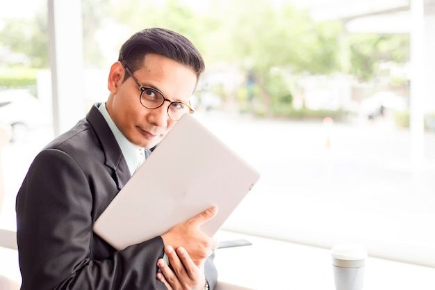 Homem de negócios da ásia trabalhando com laptop enquanto está sentado café