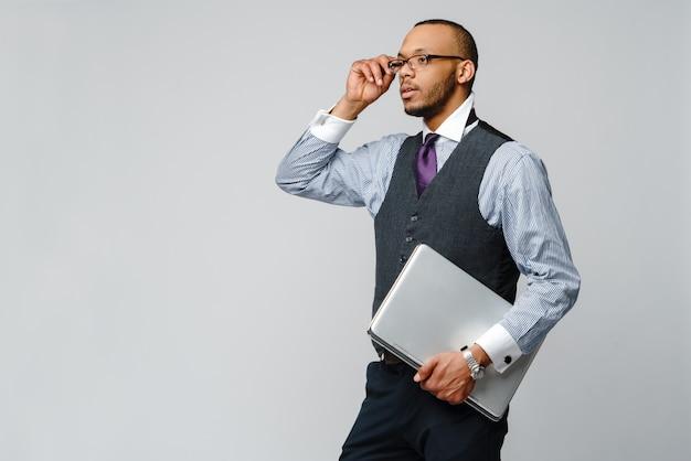Homem de negócios de afro-americano profissional segurando o computador portátil.
